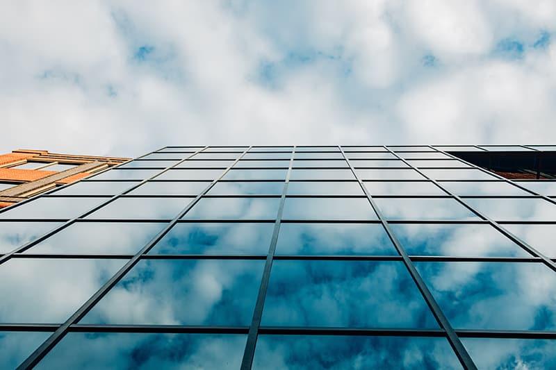 windows of building reflecting sky